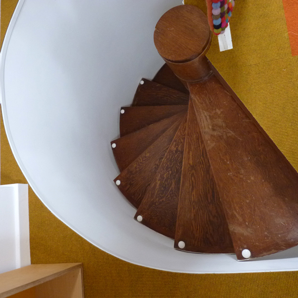 Dark wooden spiral staircase with white wall leading to mustard yellow carpet with no rails