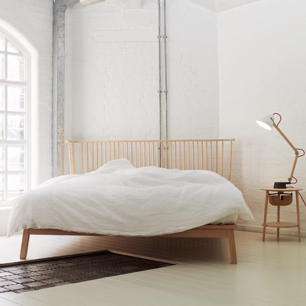 White room featuring bed with white bedding, wooden headboard, side table and lamp