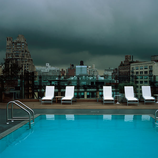 From top; stormy clouds, white sun loungers, turquoise pool